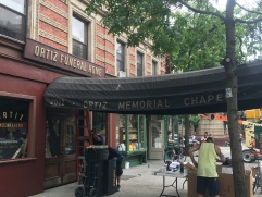 "Part of a corner deli at 60 St. Nicholas Ave is converted into a vintage funeral home for Spielberg's remake of ""west Side Story."""